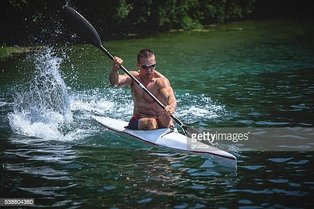 Young muscular man during kayak sprint training on still water.