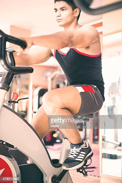Young muscular man exercising on a exercise bike in gym