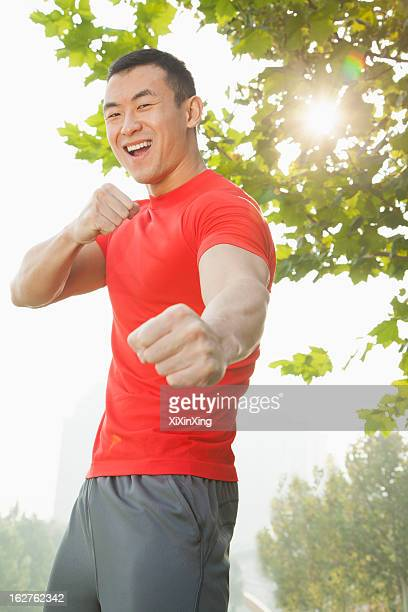 young muscular man in a fighting stance - fighting stance stock pictures, royalty-free photos & images