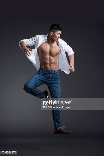 young muscular man jumping - asian six pack stock photos and pictures