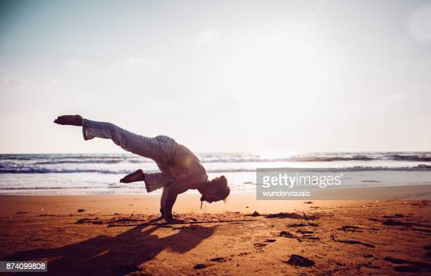 young muscular man practising yoga on the beach at sunset - acrobatic activity stock pictures, royalty-free photos & images