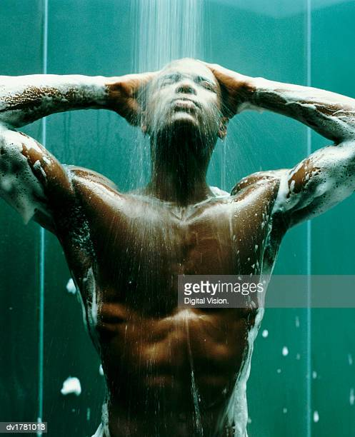 Young, Muscular Man Stands in the Shower, Covered in Soap Suds