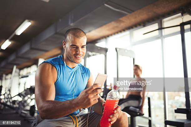 Young muscular man using mobile phone at the gym.