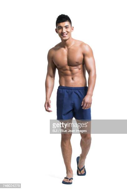 Young muscular man wearing swimming trunks