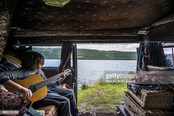a young musician palying guitar in a camper van - loch ness stock photos and pictures