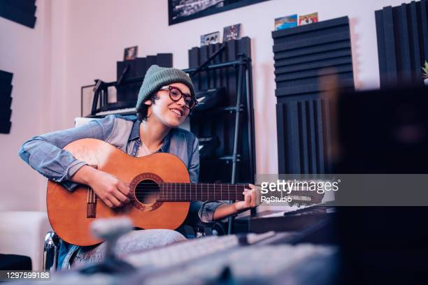 young musician playing a guitar in the music studio - singer songwriter stock pictures, royalty-free photos & images