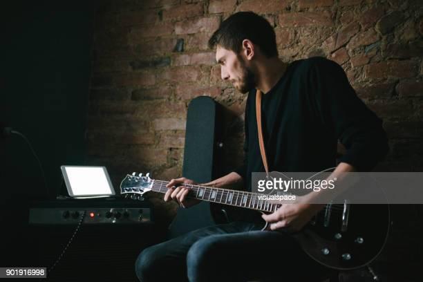 Jonge muzikant gitaarspelen Tablet kijken op versterker