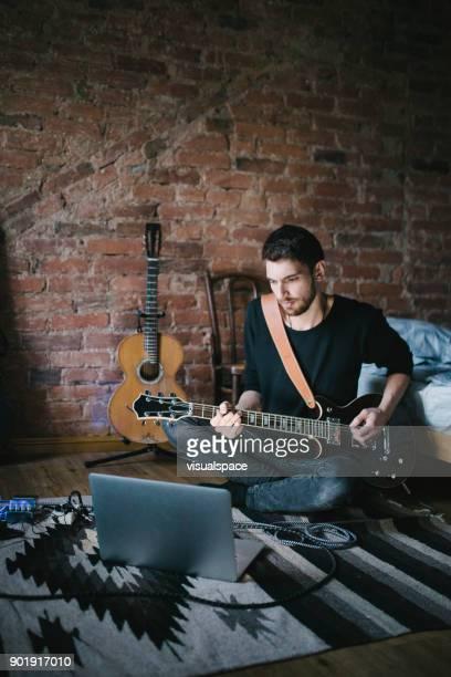 Jonge muzikant spelen gitaar zitten in de voorkant Laptop