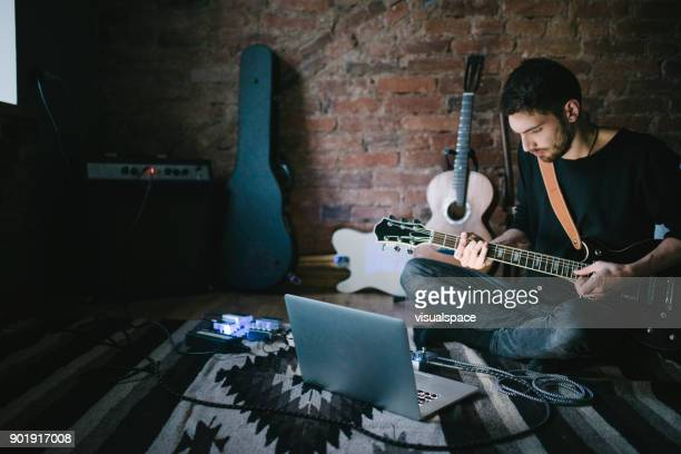 young musician playing guitar sitting in front notebook - chitarra foto e immagini stock