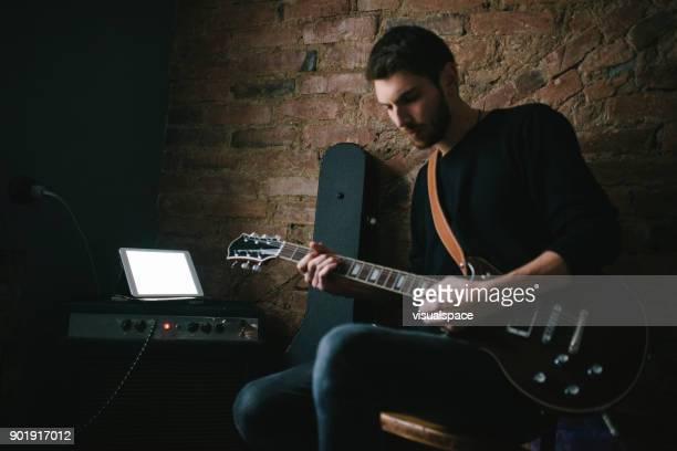 Jonge muzikant gitaarspelen met Tablet op versterker