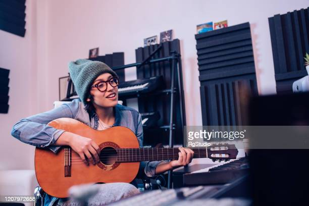 young musician playing the guitar and recording a song in the studio - songwriter stock pictures, royalty-free photos & images