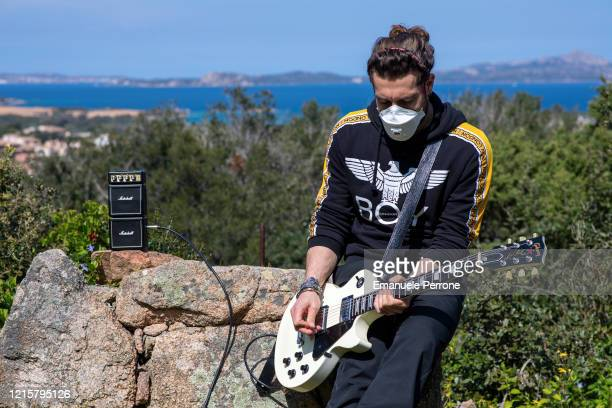 A young musician plays his guitar wearing a protective mask as imposed by the Italian Prime Minister Giuseppe Conte to counter the spread of the...