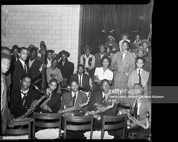 Young musicians including Nate Harper on left and Leonard Wright fourth from left with saxophones and Bobby Boswell holding bass in auditorium with...