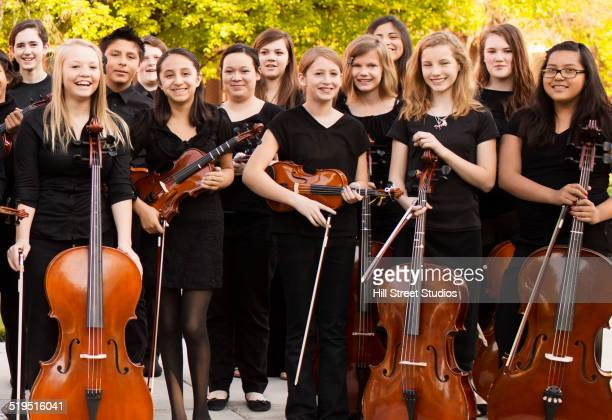 Young musicians smiling with instruments