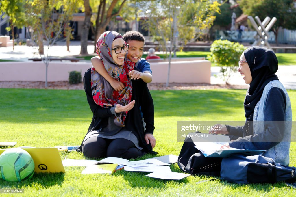 Young Muslim American mother enjoying time with her children in the park : Stock-Foto