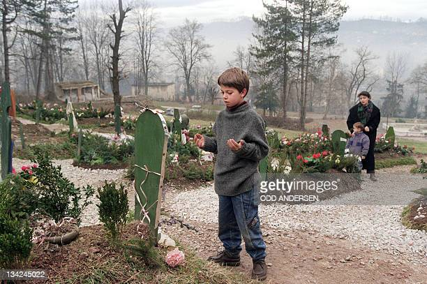 Young muslim boy prays at his brother's grave at the graveyard in Tuzla on December 25, 1995. This cemetery was dedicated to those who fell during...