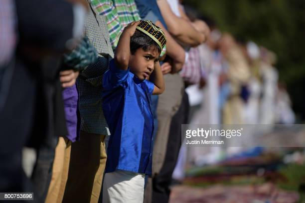 A young Muslim boy stands with the men as they pray during a celebration of Eid alFitr a holiday marking the end of Ramadan on June 25 2017 in...