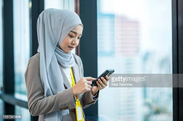young muslim business woman in skyscraper office window using smartphone, while text messaging, e-mail checking or shopping online. - hoofddeksel stockfoto's en -beelden
