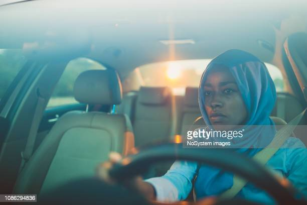 Young Muslim businesswoman driving a car