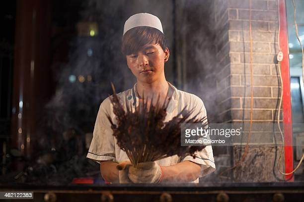 Young muslim cook holding meat skewers, at the night market in the muslim quarter of Xi'an, Shanxi, China