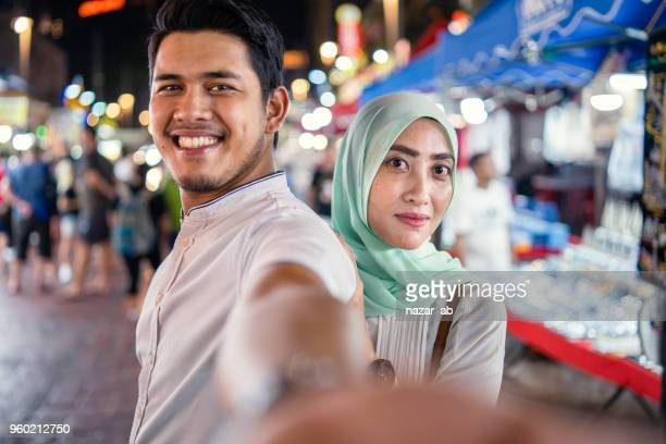 young muslim couple in food street enjoying and taking selfies. - punjab pakistan stock pictures, royalty-free photos & images