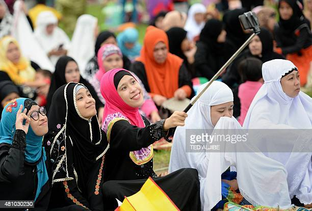 Young Muslim devotees take a 'selfie' prior to Friday prayers to mark the end of the holy month of Ramadan and the start of Eid alFitr at a park in...