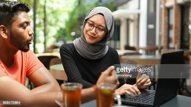 Young muslim female and male working together
