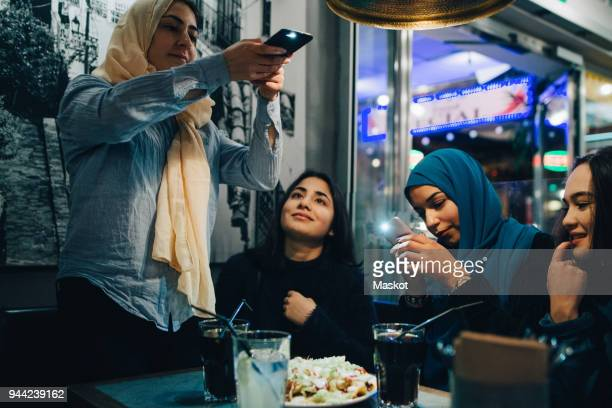 Young Muslim females photographing food and drinks on table with friends at cafe