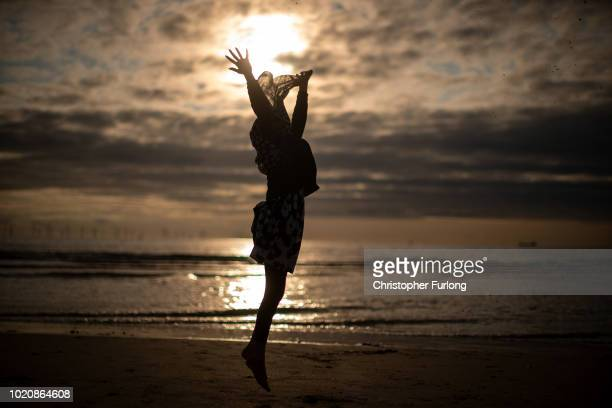 Young muslim girl dances and runs in the sea as she and her family celebrate Eid Al-Adha by watching the sunset at Crosby beach on August 21, 2018 in...
