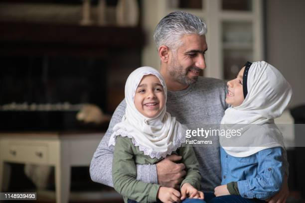 a young muslim girl enjoying cuddle time with her dad and sister - islam stock pictures, royalty-free photos & images