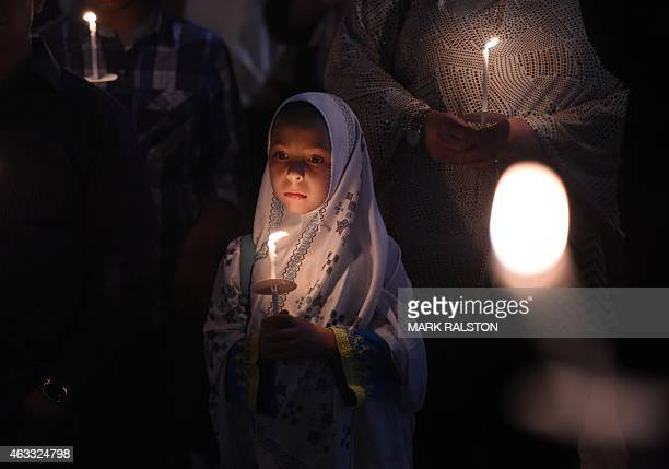 A young Muslim girl holds a candlelight during a vigil at the Islamic Center of Southern California in Los Angeles on February 12 2015 for the three...