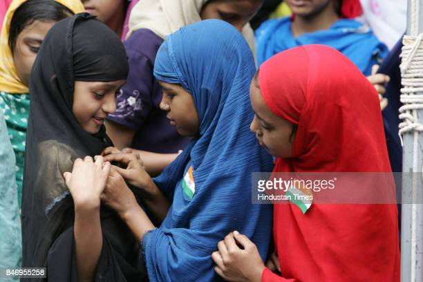 Young Muslim girls take part in the celebrations for Independence Day by pinning the National Flag on each other at Taksha Sheela Nagar in Kurla on...