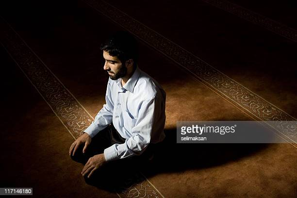 Young muslim man praying in mosque, natural day light