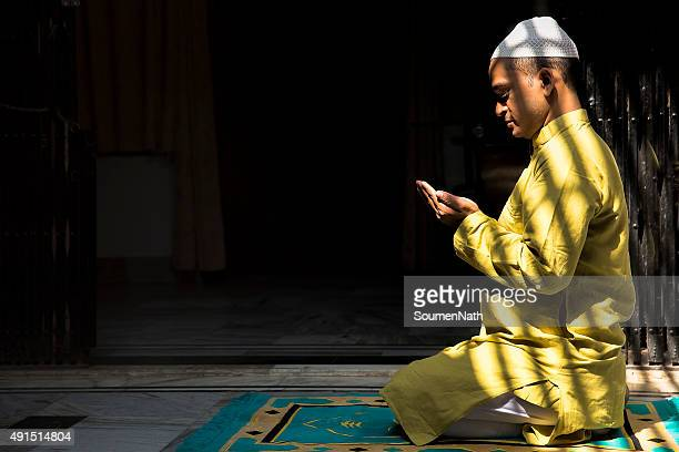 Young Muslim man praying, with folded hands
