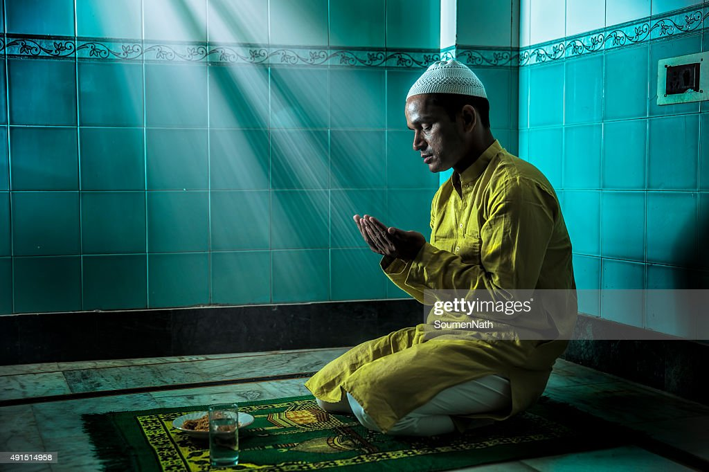 Young Muslim man praying, with folded hands : Stock Photo