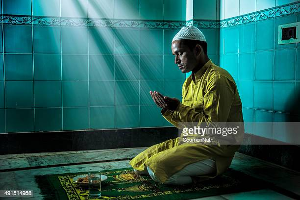 young muslim man praying, with folded hands - islam stock pictures, royalty-free photos & images