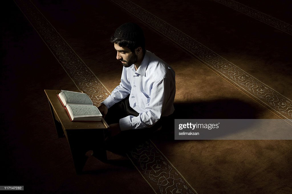 Young muslim man reading Koran in mosque : Stock Photo
