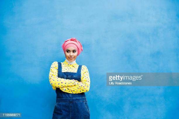 young muslim woman against a blue wall outdoors - modest clothing stock pictures, royalty-free photos & images