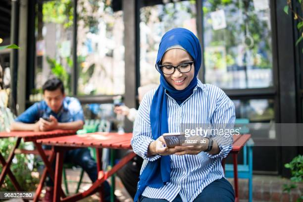 Young muslim woman checking smartphone.
