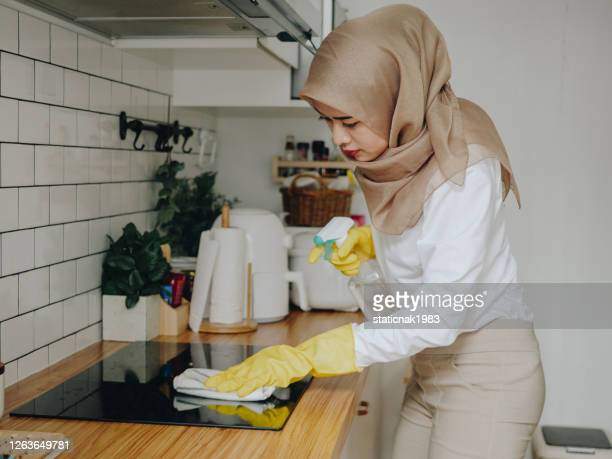 young muslim woman cleaning her kitchen counter top at home - burner stove top stock pictures, royalty-free photos & images