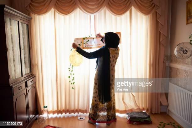 young muslim woman decorating home for ramadan gathering - bonne fete de ramadan photos et images de collection