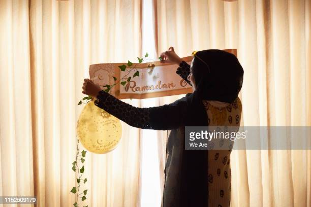 young muslim woman decorating home for ramadan gathering - ramadan decoration stock pictures, royalty-free photos & images