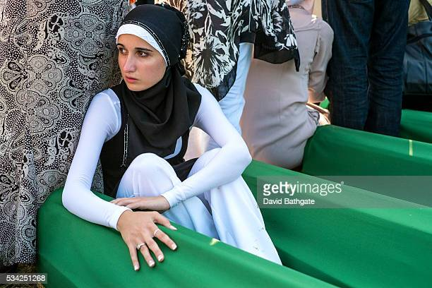 A young Muslim woman keeps watch over the remains of a family member who lost his life in the July 1995 Srebrenica massacre carried out by Bosnian...