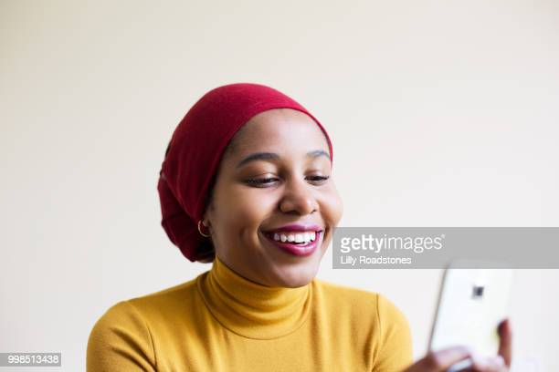 Young muslim woman laughing while using mobile phone