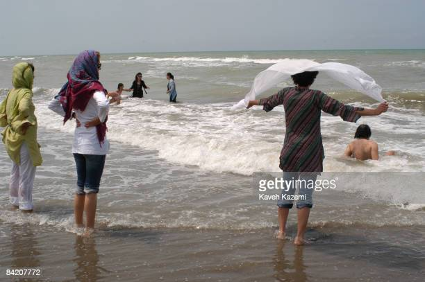 A young muslim woman lets some air into her veil on a public beach at Alamdeh on the Caspian Sea in northern Iran 10th July 2005 Iranian Islamic law...