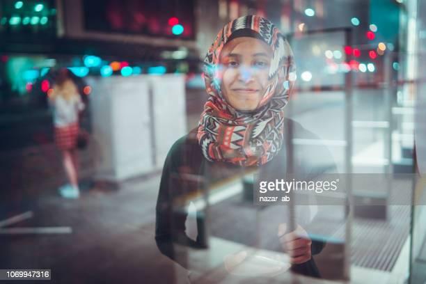 Young Muslim woman on bus stop waiting for bus.