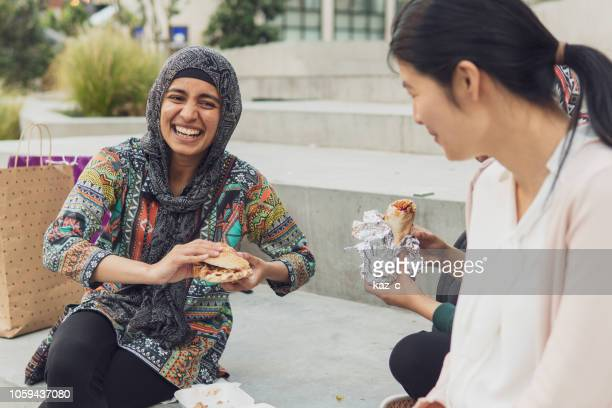 Young muslim woman out shopping and having a bite to eat with friends