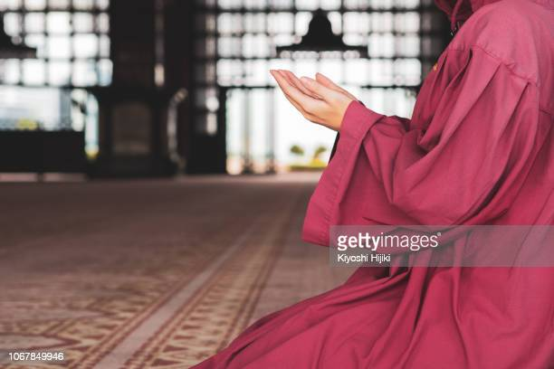 young muslim woman praying in mosque - holy quran stock pictures, royalty-free photos & images