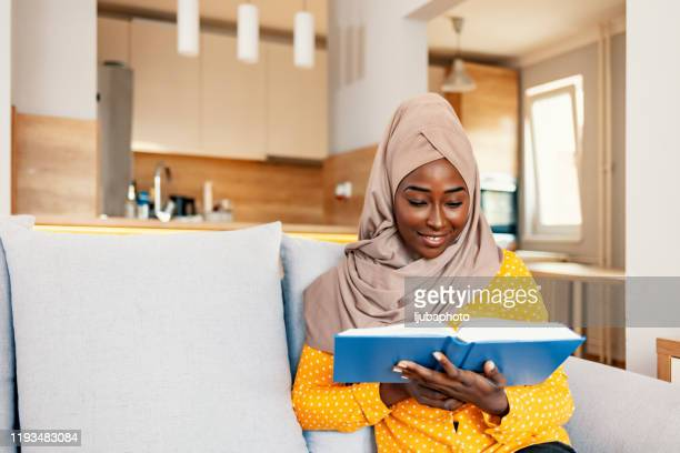 young muslim woman relaxing and enjoying her book - ghana stock pictures, royalty-free photos & images