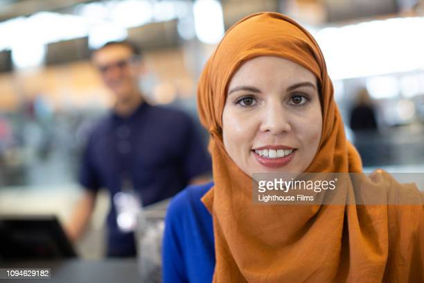 young muslim woman smiles at camera at airport check in counter. - judaism stock pictures, royalty-free photos & images